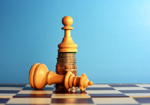 Chess pawn standing on the money over the queen