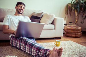 Man sitting in living room smiling at computer
