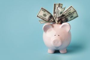Pink piggybank stuffed with dollar bills