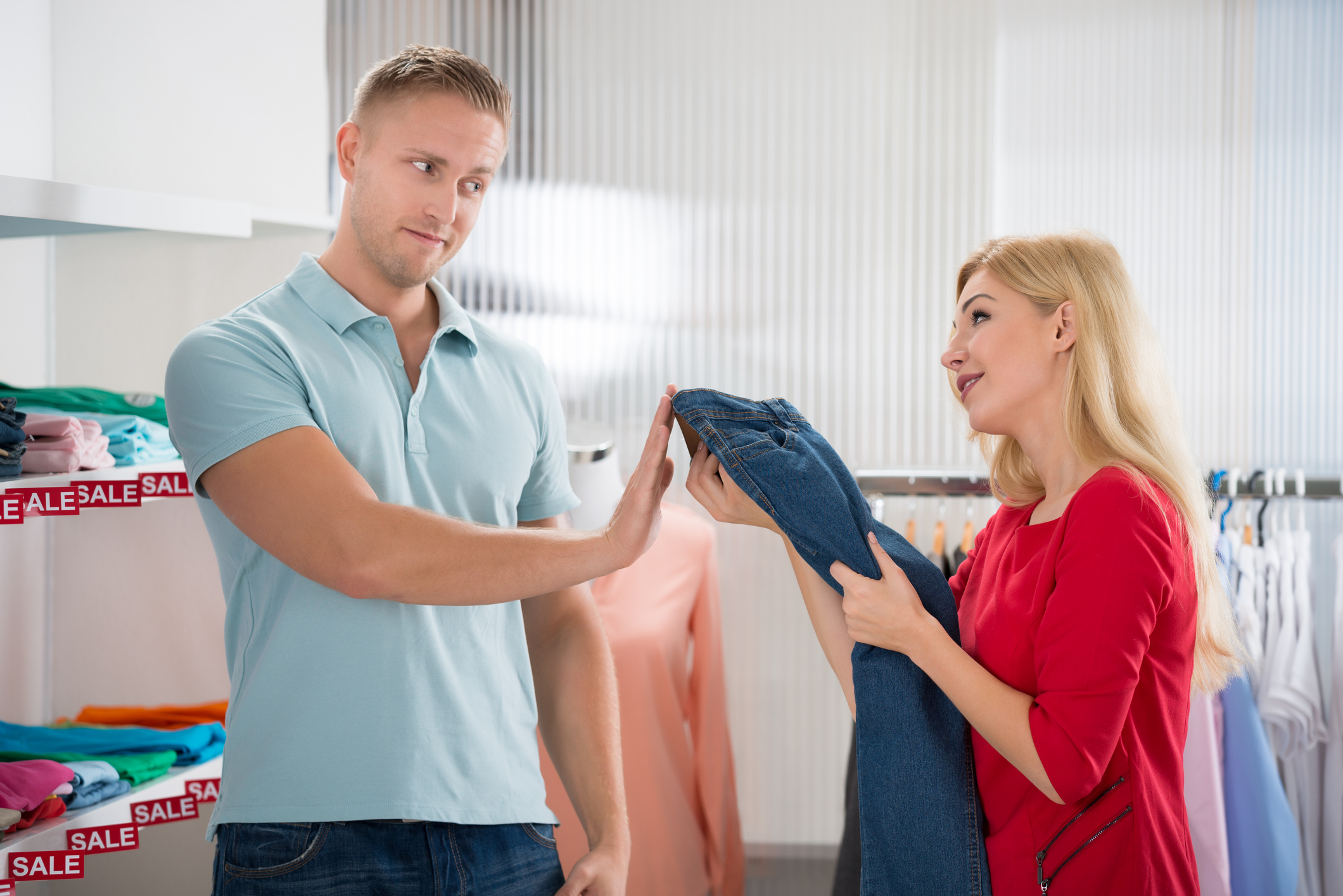 Man Showing Stop Gesture To Woman Buying Jeans