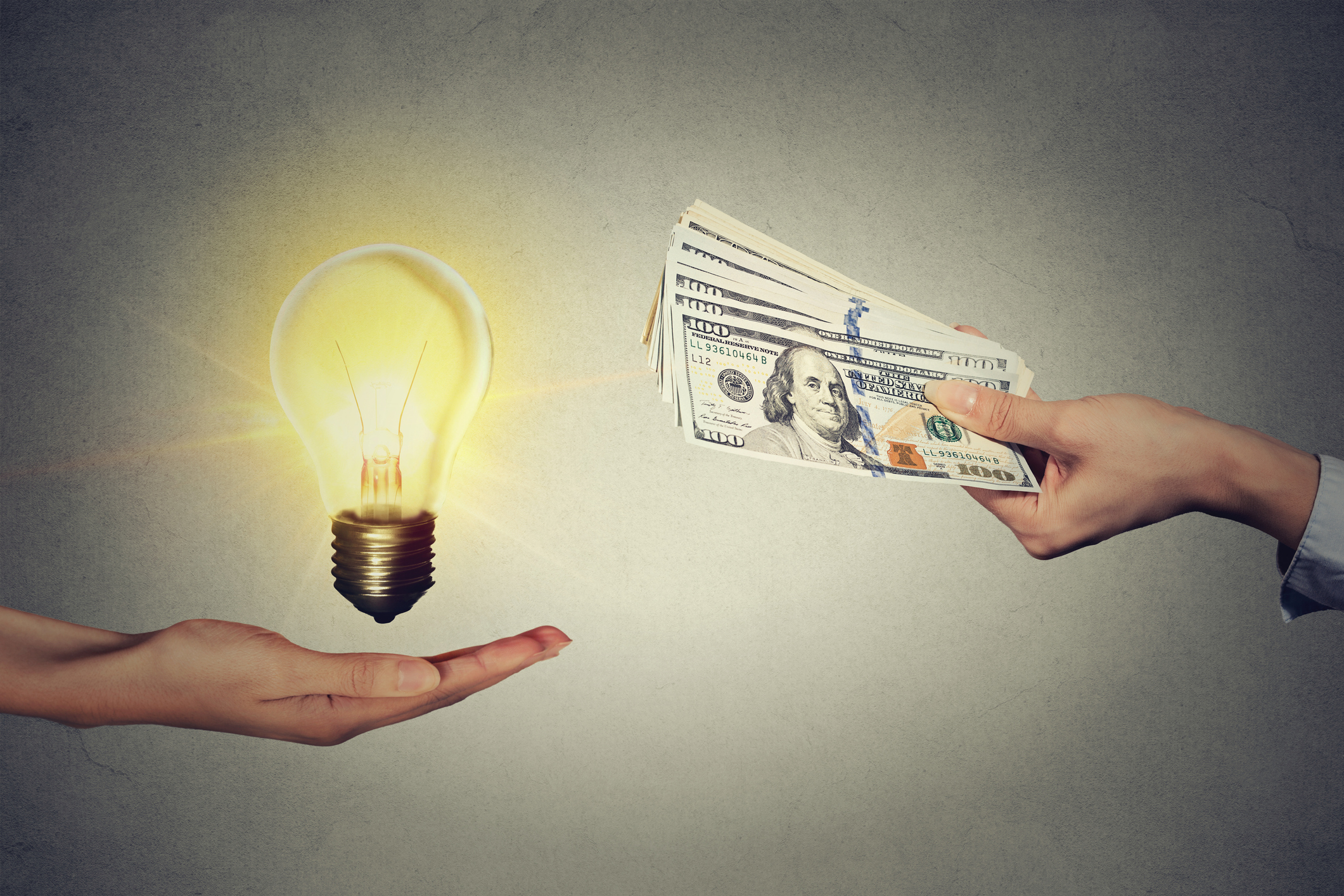one hand holding a light bulb while the other hand offers money dollar bills