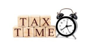 """Words """"Tax Time"""" written by wooden cubes with clock on white background."""