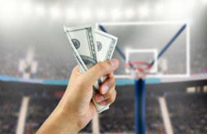 man's hand crushing a wad of hundred dollar bills in concept of getting money with bets in basketball