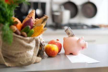 money in piggy bank and purchases from local market on table