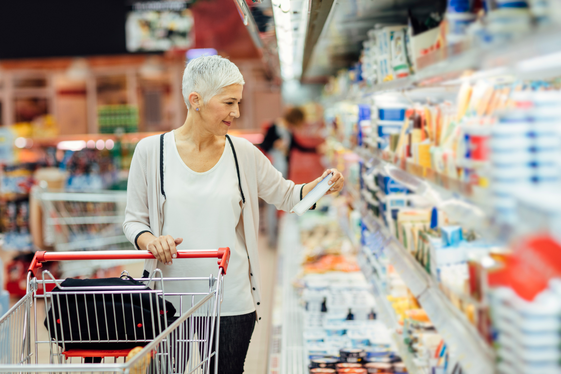 smiling woman shopping in local supermarket.