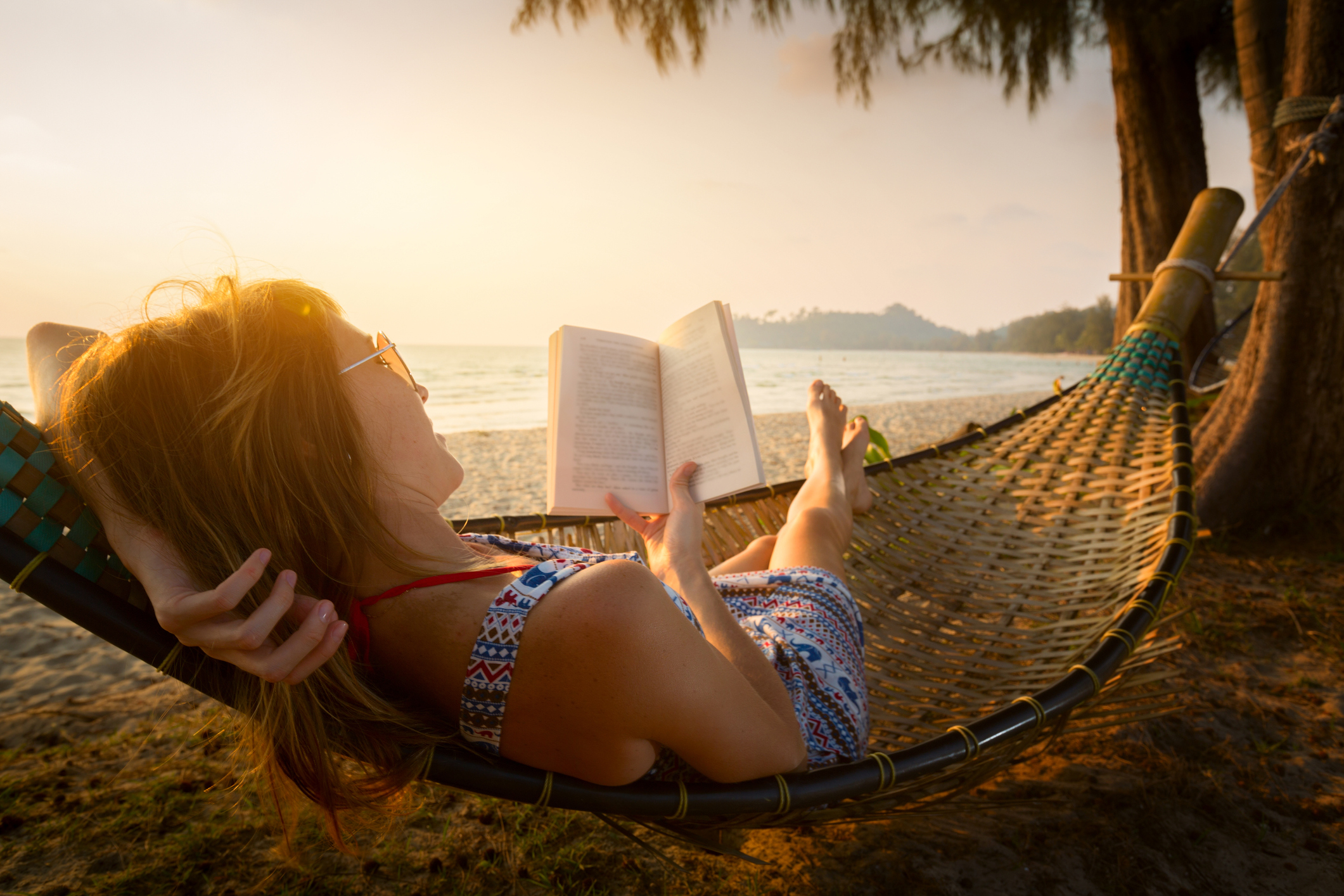 lady reading a book in hammock on a beach at sunset