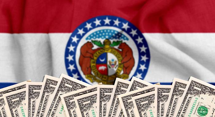 1 dollar bills in front of Missouri state flag