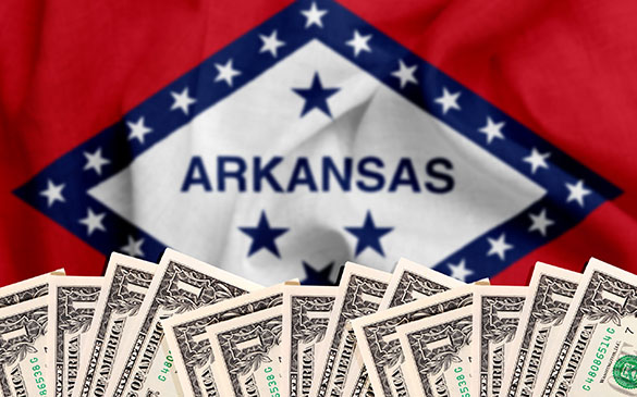 One dollar bills in front of Arkansas state flag