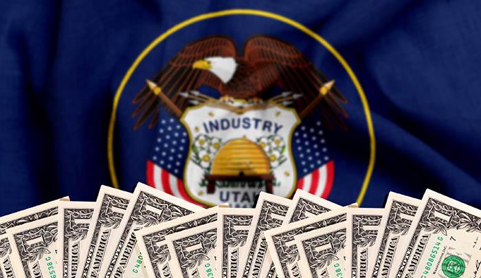 Utah flag behind row of dollar bills